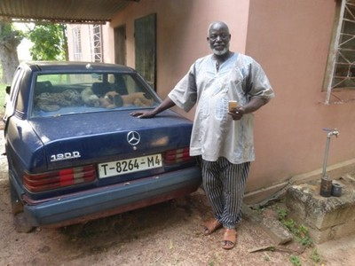 Pastor Silas Kéïta poses in front of his car bought thanks to the sale of millet and cotton from his FFF fields